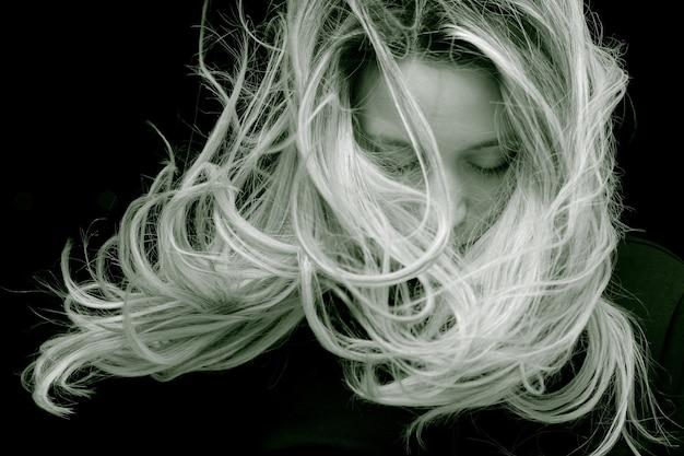 長い髪のポーズで若い女性