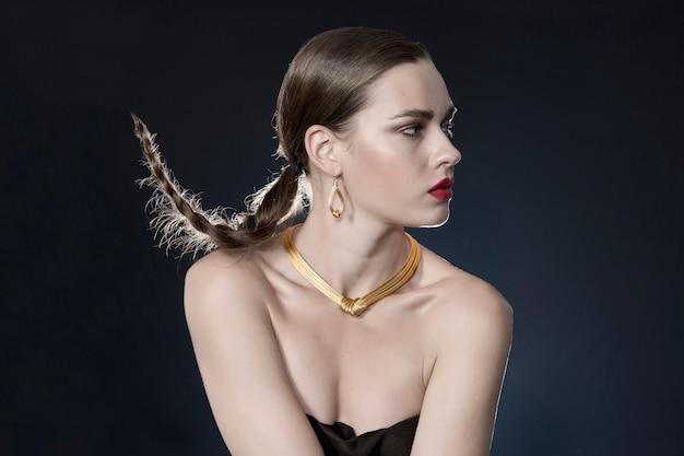 金のネックレスを持つ女性
