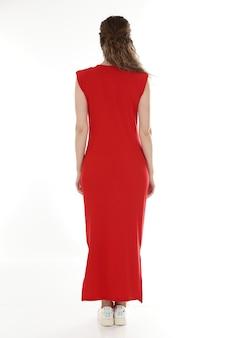 赤いドレスのポーズの女性モデル。分離された背面図