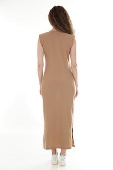 ベージュのドレスのポーズの女性モデル。分離された背面図