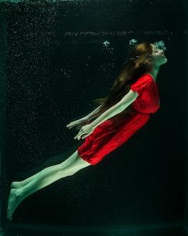水の下に赤いドレスを持つ女性