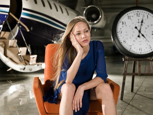 Женщина будет сидеть в аэропорту с часами рядом