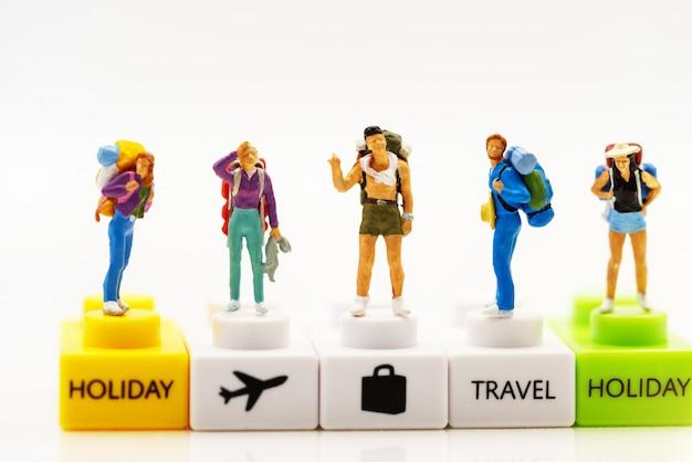 ミニチュアの人々:テキストを表彰台に隠れてバックパックを持つ旅行者