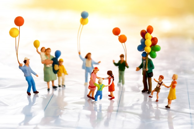 ミニチュアの人々:風船で遊ぶ子供たち。