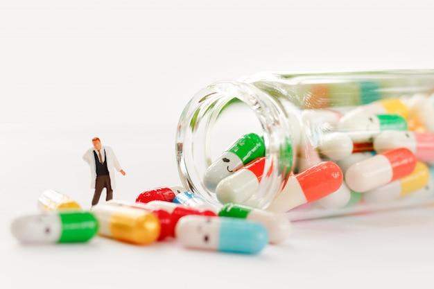 Миниатюрные люди: врач с наркотиками в качестве фона медицинской концепции