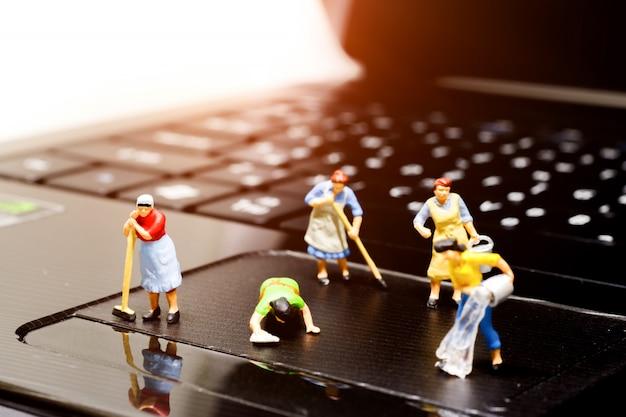 ノートパソコンを掃除するミニチュアの人々。