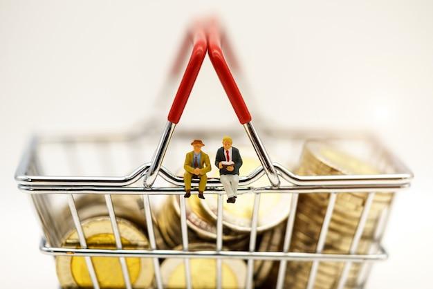 ミニチュアの人々、コインで買い物カゴの上に座っているビジネスマン