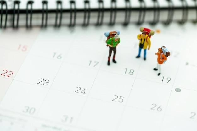 旅行カレンダーの上に立ってバックパックを持つ観光客のミニチュア