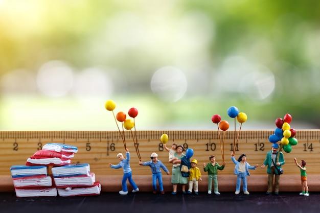 ミニチュアの人々、家族、子供たちは、定規と本でカラフルな風船を持ちます。