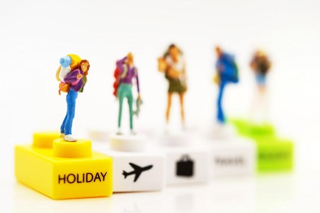ミニチュアの人々:飛行機で観光の道を歩いてバックパックを持つ旅行者。