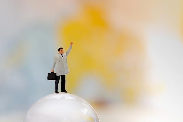 Миниатюрный бизнесмен стоя на стеклянном глобусе.