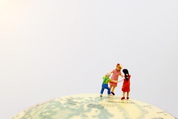 Игривые дети, взявшись за руки на планете.