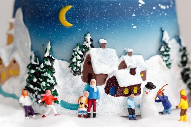 Миниатюрные люди: дети играют со снеговиком.