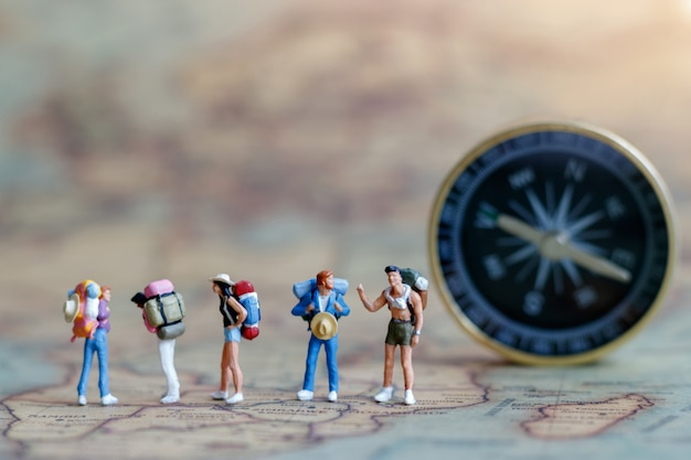 ミニチュアの人々:ビンテージマップ上に立っているバックパックを持つ旅行者。