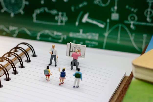 ミニチュアの人々:教師と学校の背景が付いている本の上に立っているランドセルを持つ子供。