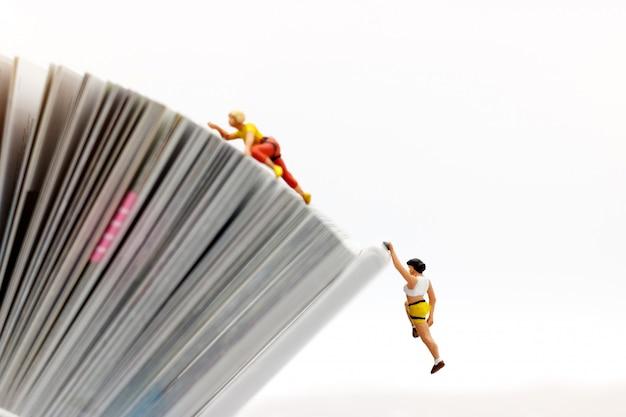 崖の上の挑戦的なルートで本を登山ミニチュアの人々、目標と成功への道の概念。