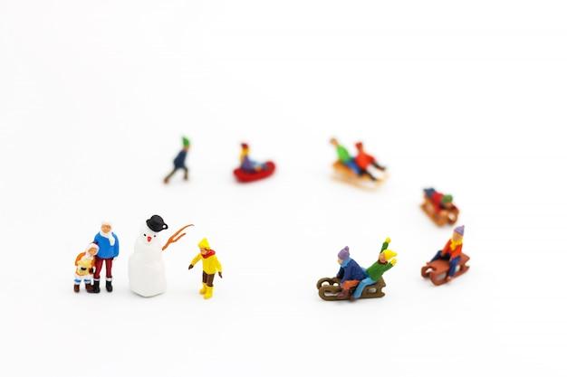 Миниатюрные люди: дети играют весело со снежным слайдером.