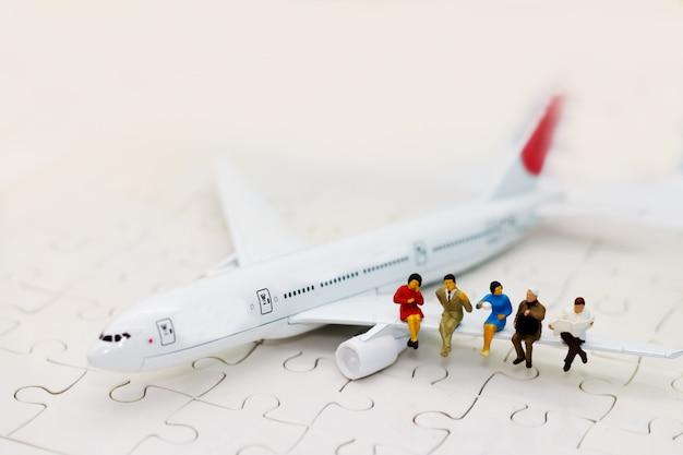 飛行機、旅行、ビジネスコンセプトに座っているミニチュアビジネス人々。
