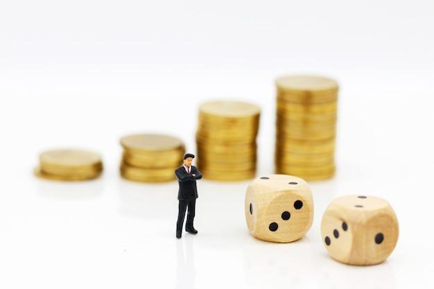 ミニチュアの人々:サイコロとコインスタックで立っているビジネスマン。投資リスクの概念。