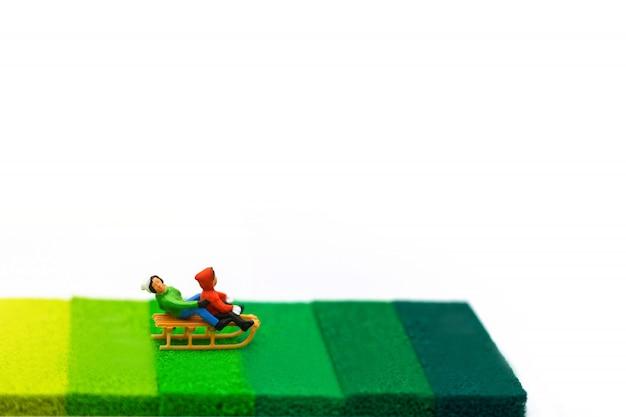 ミニチュア人、雪のスライダーで遊んでいる子供たち