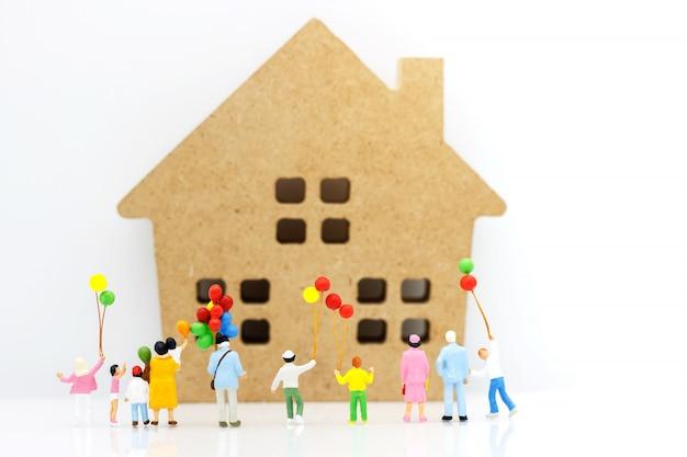 Миниатюрные люди: семья и дети наслаждаются с красочными воздушными шарами и домом, счастливая концепция дня семьи.