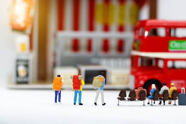 バスを待っている荷物を持つミニチュアの人々。交通手段。
