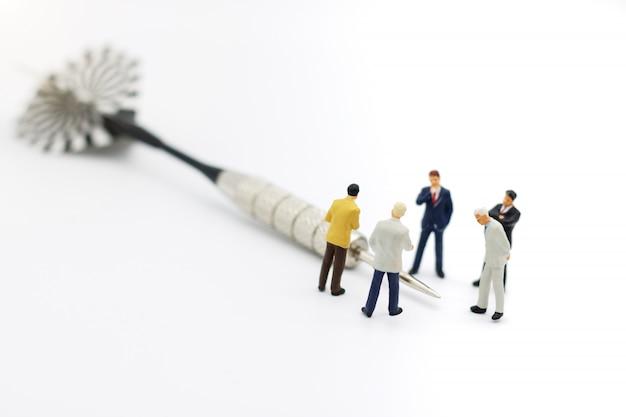 Миниатюрные люди: бизнес команда стоя с дротиком.