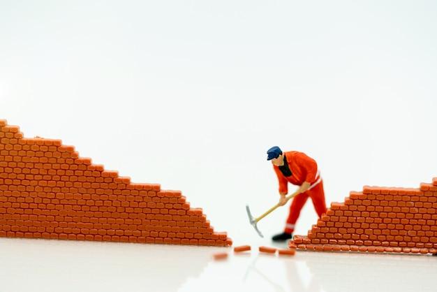 ミニチュアの人々:労働者は世界の前に壁を修理します。