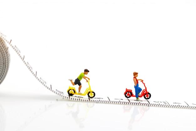 ミニチュアの人々、子供たちが自転車で遊ぶ