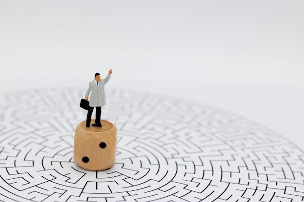 ミニチュアの人々:サイコロと迷路の中心に立っているビジネスマン。