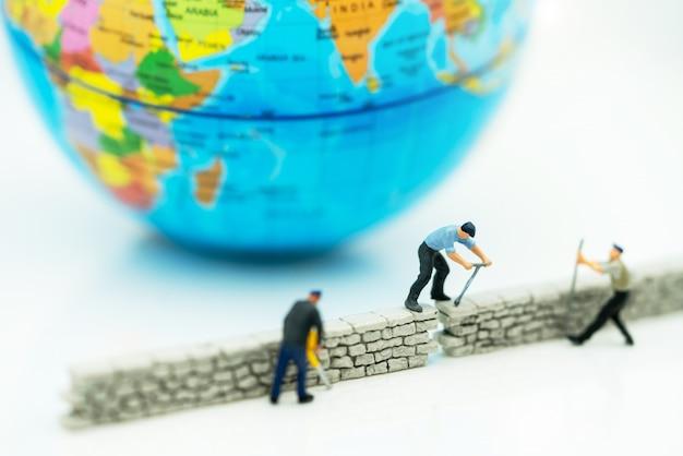 Миниатюрные люди: рабочий чинит стену перед миром. концепции решения проблем.
