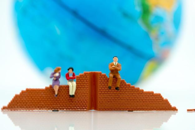 Миниатюрные люди: бизнесмен, стоящий со стеной и миром. концепции решения проблем.
