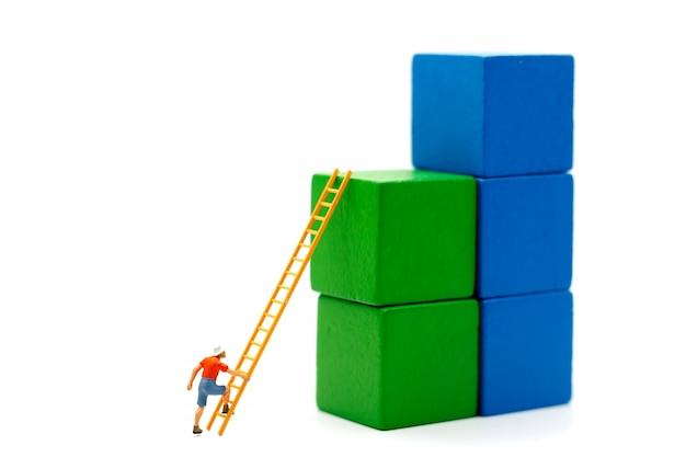 Миниатюрные люди: альпинист, смотрящий вверх по сложному маршруту на графике роста с деревянной лестницей, концепция пути к цели и успех.