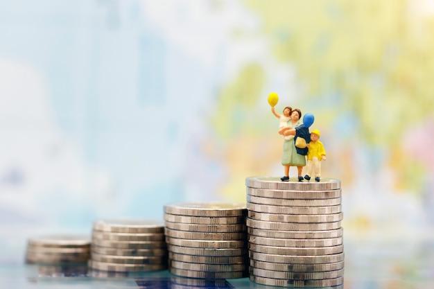 Миниатюрные люди: счастливая семья стоит на стопке монет, экономит деньги. деньги сбережений, образование, план на случай чрезвычайных ситуаций и финансовая концепция.