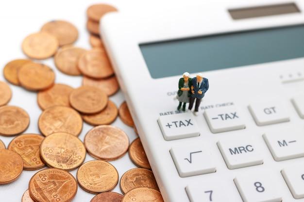 Миниатюрные люди: счастливые старые люди стоя на калькуляторе с стогом монеток, планированием выхода на пенсию, планом на случай чрезвычайных обстоятельств, страхованием жизни и финансовой концепцией.