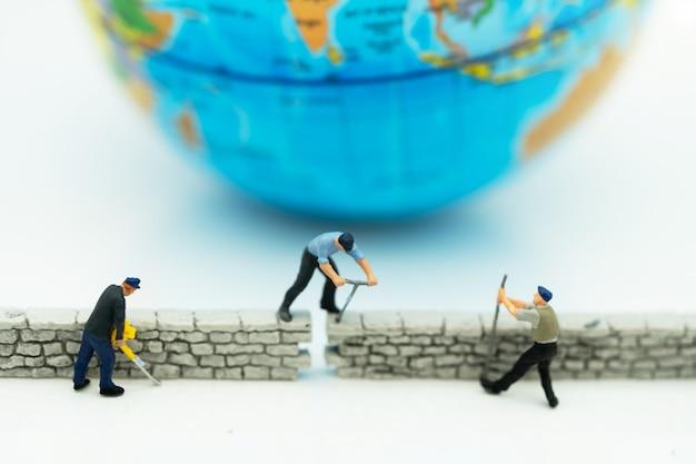 ミニチュアの人々:労働者は世界の前に壁を固定します。