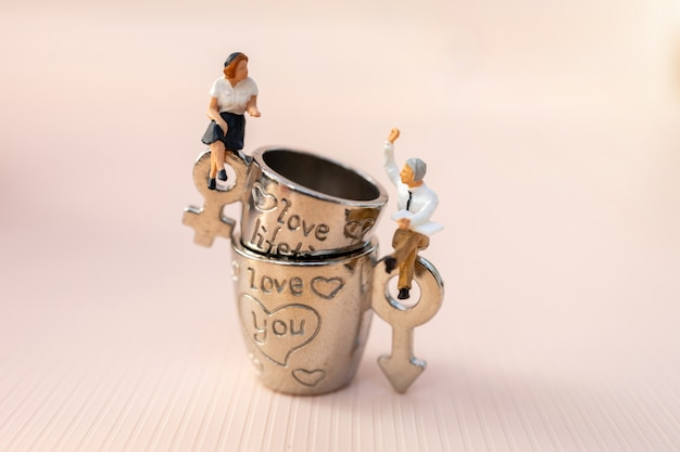 ピンクの背景、素敵なコンセプトとして、ミニチュアの人々カップルの恋人がコーヒーを片手に座っています。