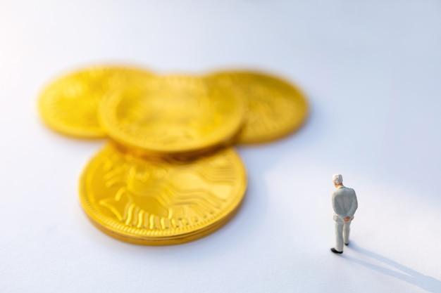 ミニチュアの人々:ビジネスマンは立って、金貨、ビジネスコンセプトの成長について考えます。