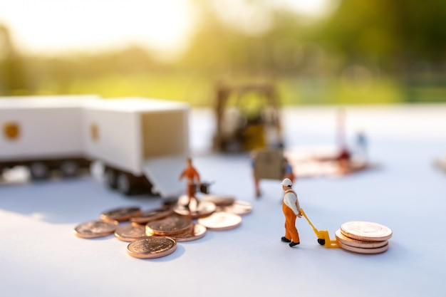 ミニチュアの人々:労働者はボックスとコインをトラックコンテナーにロードします。配送とオンライン配信サービスのコンセプト。