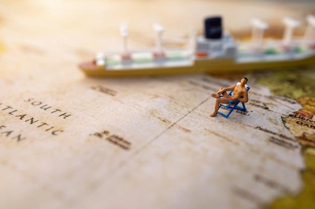 ミニチュアの人々はビンテージ世界地図と船、旅行、夏のコンセプトのビーチの日光浴用の席に座っています。
