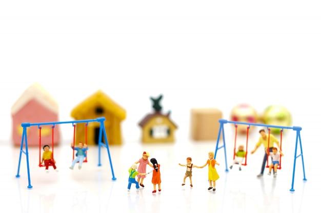 Миниатюрные люди, дети и семья наслаждаются качелями.