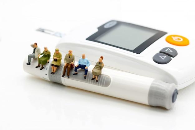 糖尿病の血糖値計の上に座っているミニチュアの人々。