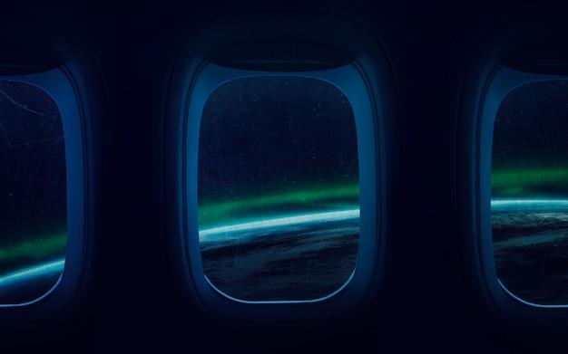 宇宙船の窓に地球惑星の美しさ。