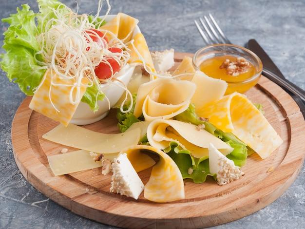 Ассорти из сыра с медом на деревянной доске