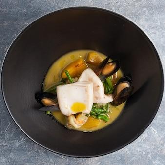 Морепродукты: креветки, мидии, кальмары, морской гребешок в соусе из зеленого карри. вид сверху