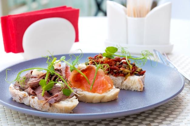 皿に盛り合わせのブルスケッタ:サーモン、牛肉、野菜。選択したフォーカス。