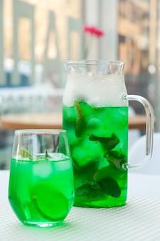 Холодный зеленый мятный лимонад в графине и в стакане