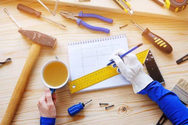 Блокнот с чертежами и строительными инструментами.