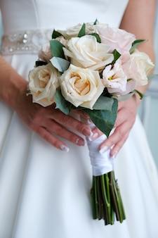 Свадебный букет с розовыми и белыми розами в руках невесты.