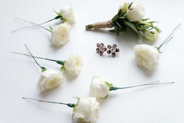 白いバラと緑の葉の新郎のブートニア。花とイヤリングの花嫁の近く。結婚式の道具とアクセサリー。